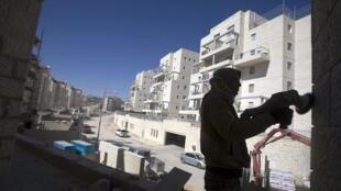 Un ouvrier palestinien travaille sur le chantier d'une colonie juive près de Jerusalem, appelé Har Homa par les Israéliens,  et Jabal Abu Ghneim par les Palestiniens, le 22 mars 2010.