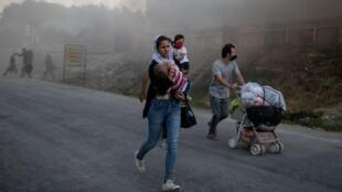 Une famille fuit les flammes lors de l'incendie du camp de Moria sur l'île de Lesbos, le 9 septembre 2020.