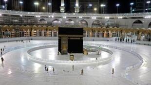 Des policiers saoudiens gardent la Kaaba, la pierre noire, dans l'enceinte de la Mosquée sacrée de La Mecque, interdite aux rassemblements pour lutter contre le coronavirus, le 24 avril 2020.