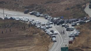 Des colons se rassemblent non loin du lieu où deux Israéliens ont été tués, la veille, le 2 octobre 2015 en Cisjordanie.