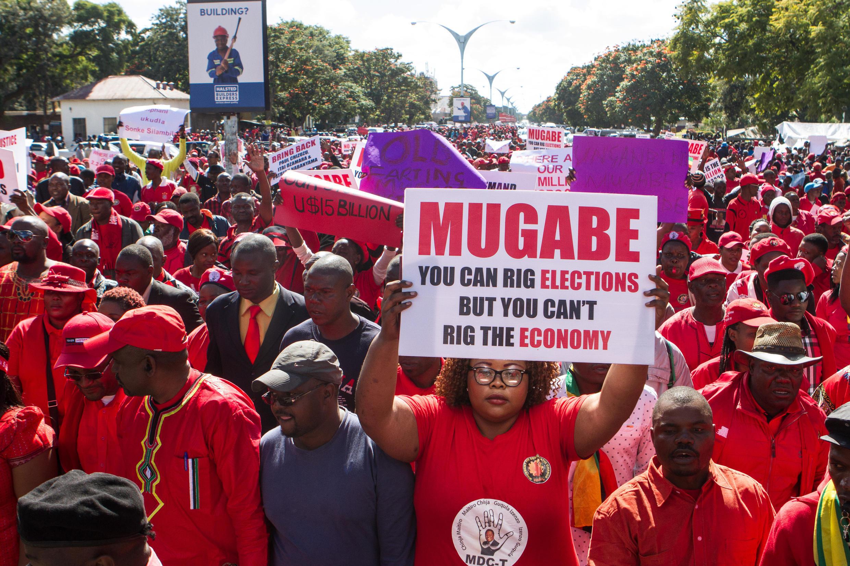 Une manifestante brandit une pancarte « Mugabe, tu peux truquer les élections mais pas l'économie», à Bulawayo, au Zimbabwe.