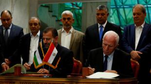 Saleh Arouri, líder da delegação do Hamas e Azzam Ahmad da do Fatah assinando a reconciliação no Cairo 12/102017