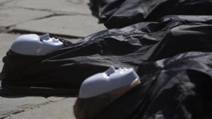 Les militants de la Coalition pour le contrôle des armes, dans de faux sacs mortuaires devant le siège de l'ONU, le 2 juillet 2012 à New York.