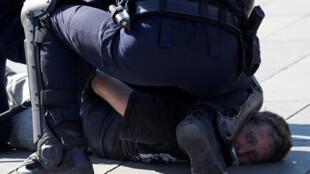 Un policier arrête un manifestant lors de l'acte XXIII du mouvement des «gilets jaunes» à Paris, le 20 avril 2019.