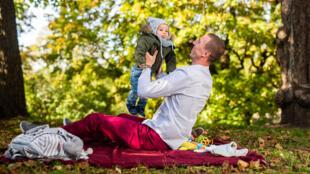 Un bébé joyeux et son papa dans un parc en Norvège.