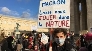 "VivIen, who home-schools his two sons, holds a banner reading ""Macron, leave us to play outside""."