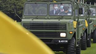 El presidente colombiano Iván Duque (C) viaja en un camión militar junto a su nuevo ministro de Defensa Diego Molano (I) durante una ceremonia en la escuela militar de Bogotá, el 6 de febrero de 2021