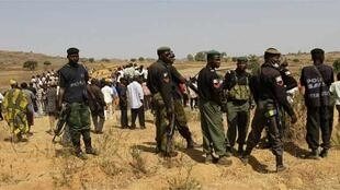 Police stand guard during a mass burial in  Dogo Nahawa village