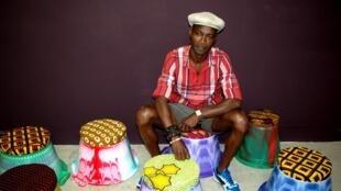 Jean-Servais Somian et ses bassines en plastique surmontées de coussins en wax.