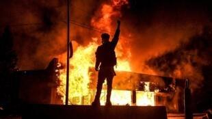 Un manifestant devant un bâtiment incendie dans la ville américaine de Minneapolis dans la nuit du 29 au 30 mai 2020