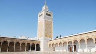Vue d'une mosquée et son minaret au centre.