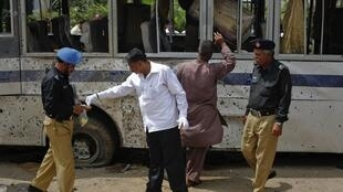 Security officials collect evidence at the site of  bomb blast in Karachi 28 April, 2011