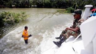 Un militar sobre un blindado recorre una calle inundada durante una misión de rescate en el pueblo de Bulathsinhala en Sri Lanka el 27 de mayo de 2017.