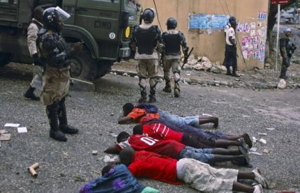 Supporters of Michel Martelly lie on the ground after they were arrested during a protest in Petion Ville