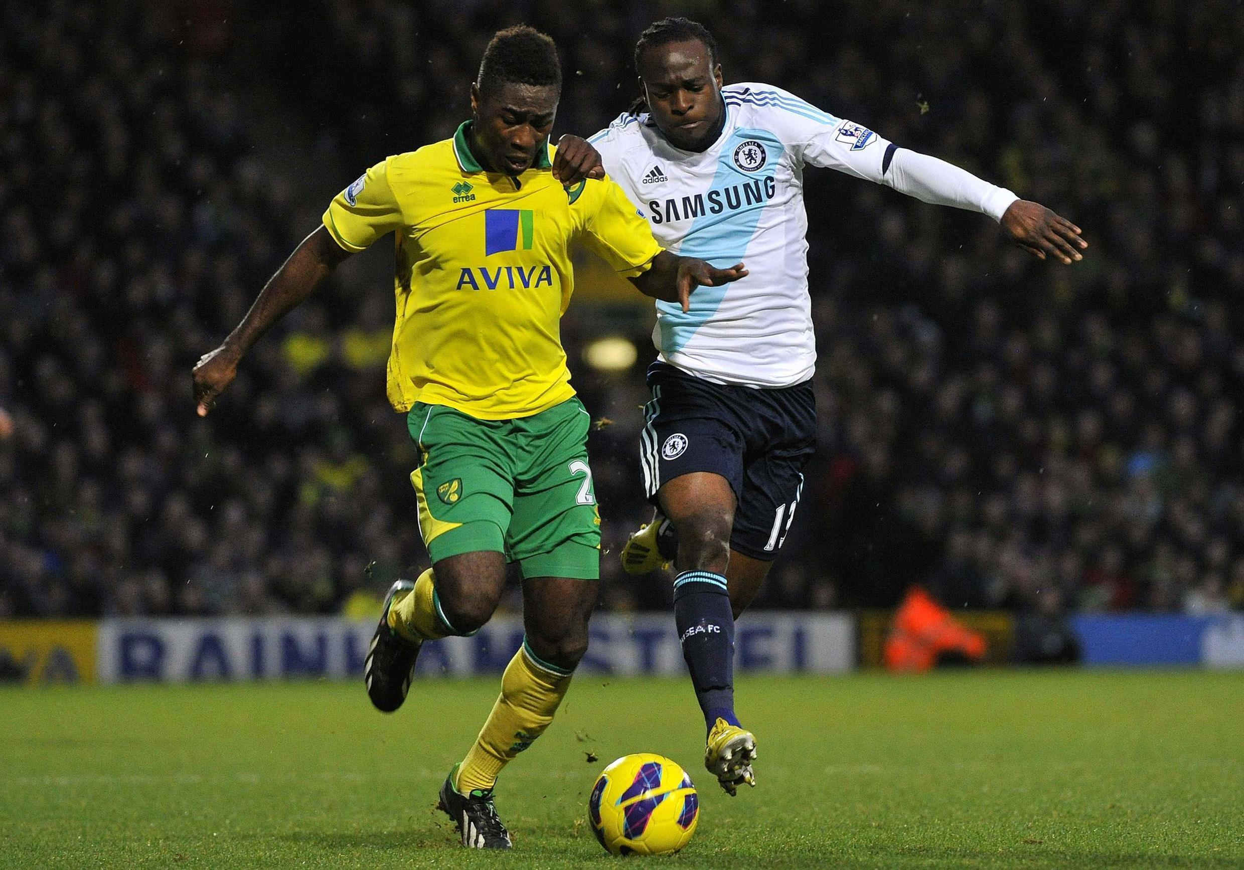 Norwich City's Alex Tettey (L) challenges for the ball with Chelsea's Victor Moses, 26 December, 2012