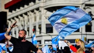 People wave Argentine flags during a protest in Buenos Aires against the government's tight lockdown measures against the spread of the novel COVID-19 coronavirus