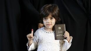دختر خردسال با در دست داشتن شناسنامه مادرش در یکی از حوزههای رأیگیری در جنوب تهران. ۲۹ اردیبهشت/ ١٩ مه ٢٠۱٧