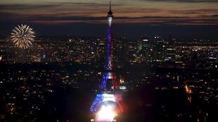 Fireworks light up the sky as the Eiffel Tower is illuminated in the colors of the French flag.