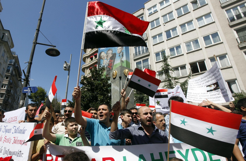 Waandamanaji nchini Syria wakipeperusha bendera za nchi hiyo wakishinikiza Rais Bashar Al Assad aondoke madarakani