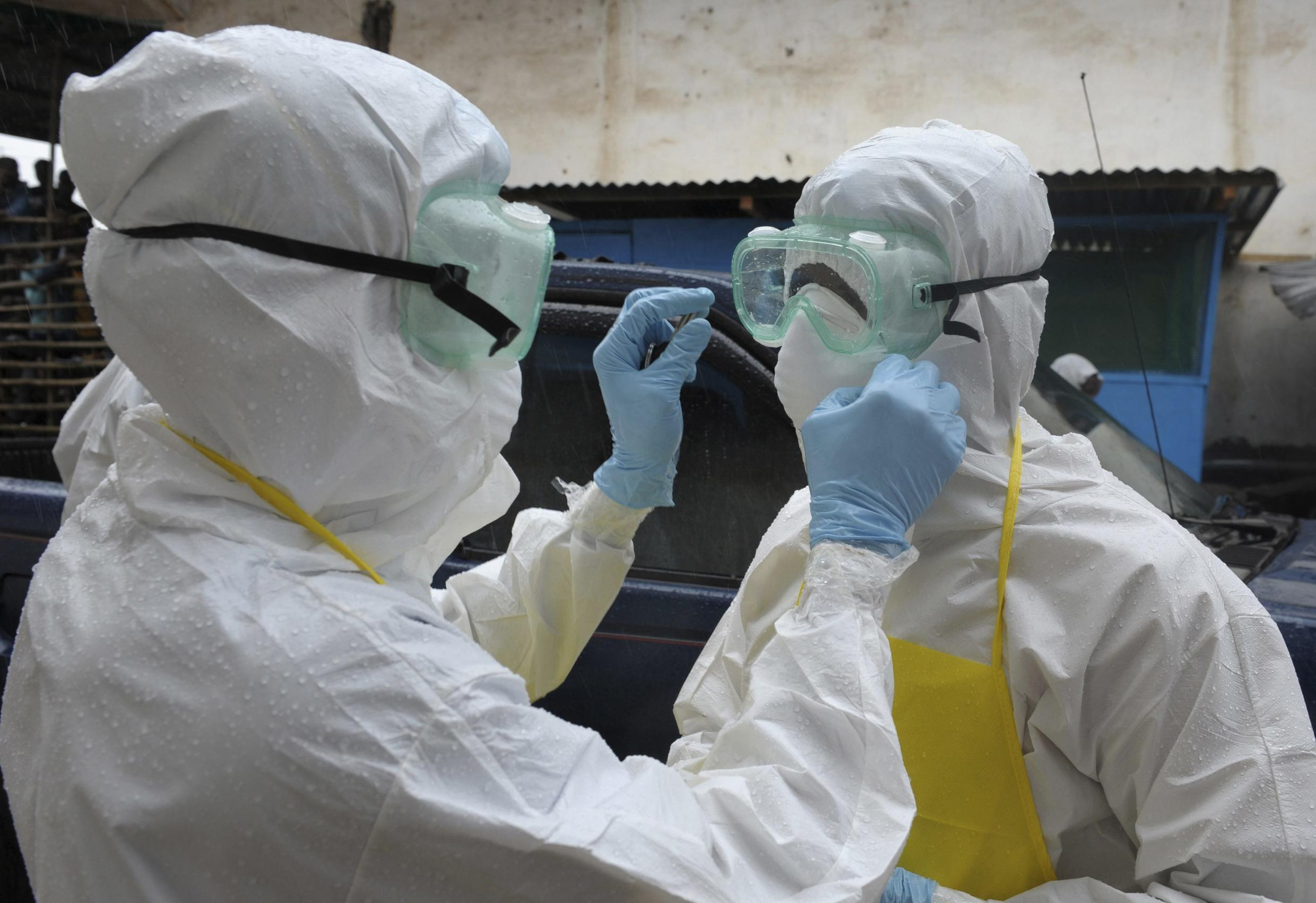 Medical personnel in protective suits treat Ebola in Liberia