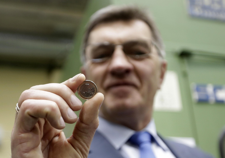 Альгирдас Буткевичус, премьер-министр Литвы на монетном дворе демонстрирует литовскую монету в 1 евро 16/07/2014