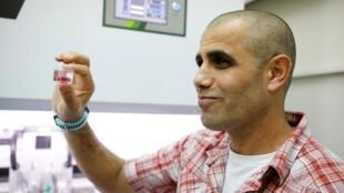 Le scientifique israélien Tal Dvir tient un bocal transparent contenant ce qui est, selon l'université de Tel-Aviv, le premier cœur artificiel vascularisé au monde imprimé en 3D, le 15 avril 2019.