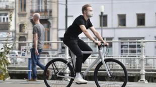 Un hombre con mascarilla protectora monta en una bicicleta eléctrica el 28 de julio de 2020 por una calle de Bruselas