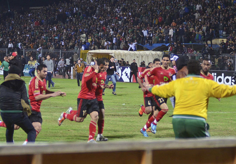 Os jogadores do Al Ahly tentam deixar o estádio no meio do tumulto nesta quarta-feira.