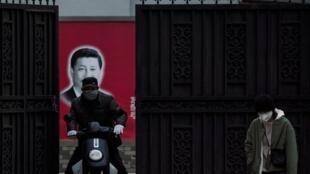 Com uma máscara de proteção improvisada, morador de Xangai circula próximo a local com grafite do presidente chinês, Xi Jinping.