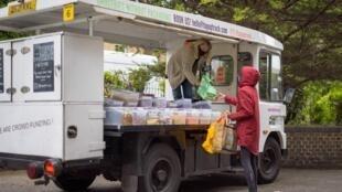 La fundadora de Topup Truck, Ella Shone (izq.), atiende a una clienta desde su camión convertido en una tienda de cero residuos en el este de Londres, el 21 de mayo de 2021