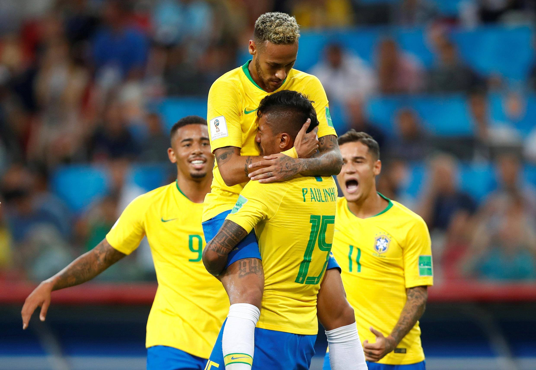 Neymar celebra no colo de Paulinho o gol do meio-campista, que abriu o placar contra a Sérvia, em 27 de junho de 2018.