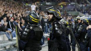 Policiais dentro do gramado para conter o tumulto entre torcedores do Lyon e do Besiktas no jogo pela Liga Europa.