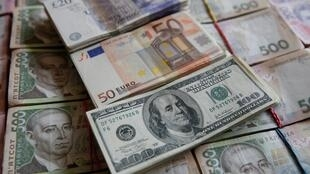 Des billets de banque en hryvnia de 100 dollars, 50 euros et 20 ukrainiens et 500 ukrainiens.