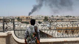 Un combattant kurde des YPG observe la ville de Raqqa, en Syrie, après une frappe de la coalition, le 16 juin 2017.