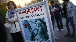 Tourists stand next to a sign announcing the closure of the Statue of Liberty, New York, 1 October, 2013