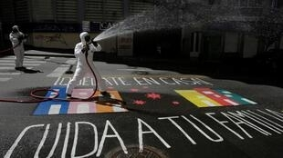 Désinfection d'une rue avec un graffiti au sol où l'on peut lire «Restez à la maison, prenez soin de votre famille» alors que la propagation du Covid-19 se poursuit à La Paz, le 14 avril 2020.
