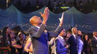 À Abuja au Nigeria, au Hilton, dans la «salle du trône», qui fait office de lieu de culte. Au premier plan les mains levées: le pasteur Tunde Benjamins-Laniyi.