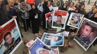 Des Egyptiens protestent en montrant des photos des morts tombés pendant la révolution.