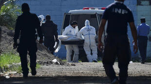 Forensic experts take away a corpse from the women's prison in Tamara, Honduras following the murder of six inmates