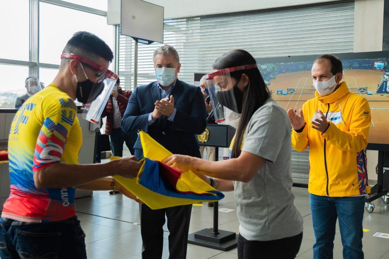 Mariana Pajón, bicampeona olímpica de BMX y Sergio Higuita, campeón nacional de ciclismo, recibieron la bandera colombiana en representación de los deportistas viajeros. La entregó en presidente Iván Duque en Bogotá.