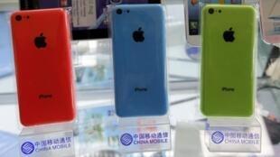 """Varios Iphones expuestos en un presentador con el logo de """"China Mobile"""",  Pekín, 23 de diciembre de 2013."""