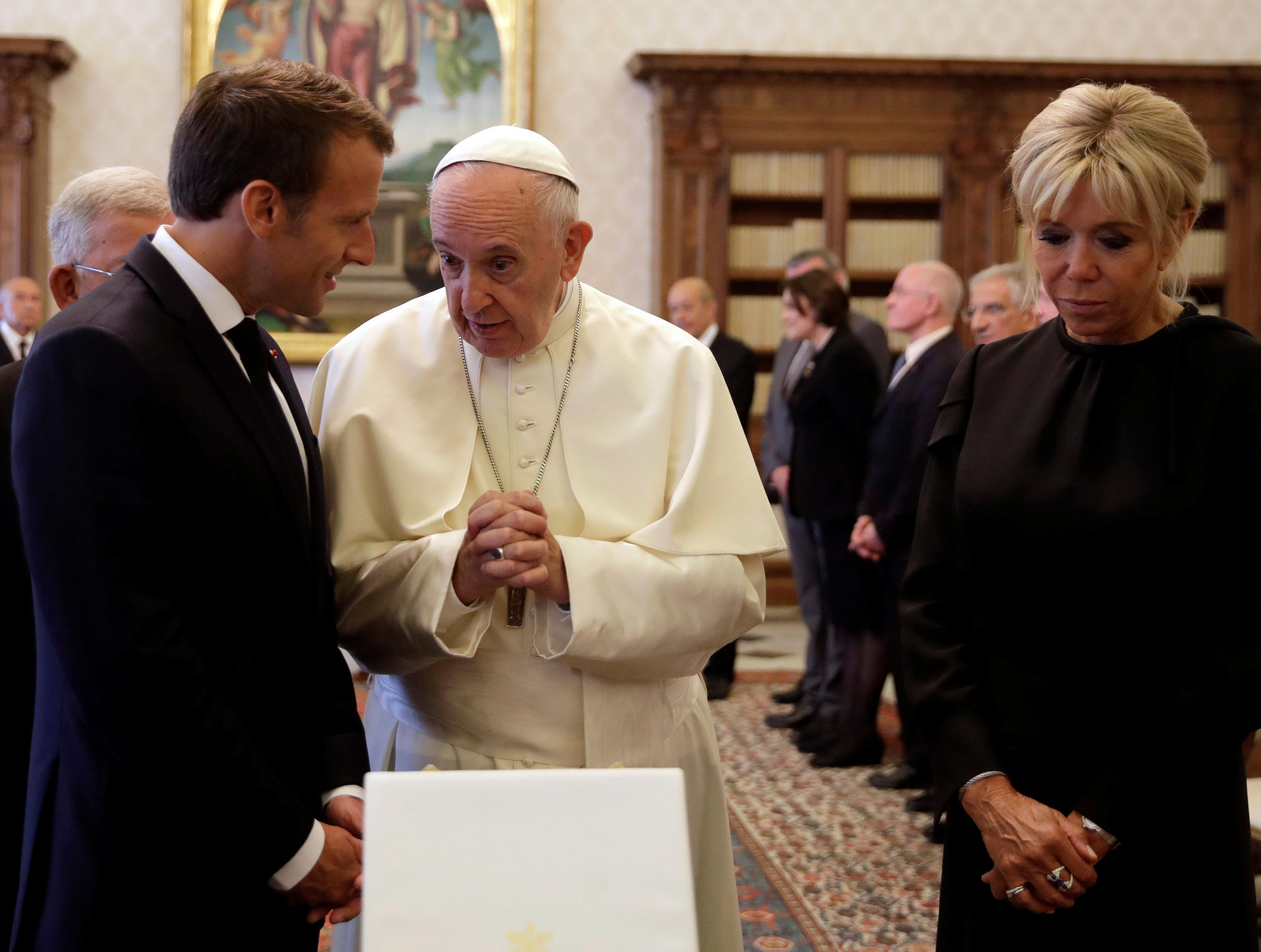 Pope Francis exchanges gifts with French President Emmanuel Macron and his wife Brigitte during a private audience at the Vatican, June 26, 2018.
