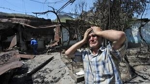 Un Ouzbek devant les restes de sa maison brûlée dans la ville d'Och, dans le sud du pays, le 14 juin 2010.