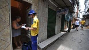 Un postier dans la Favella de Rocinha le 14 décembre 2011. Depuis la pacification,  la municipalité de Rio de Janeiro  a commencé à régulariser le quartier, en nommant les rues et les bâtiments, permettant à ses habitants de recevoir du courrier  à leur do