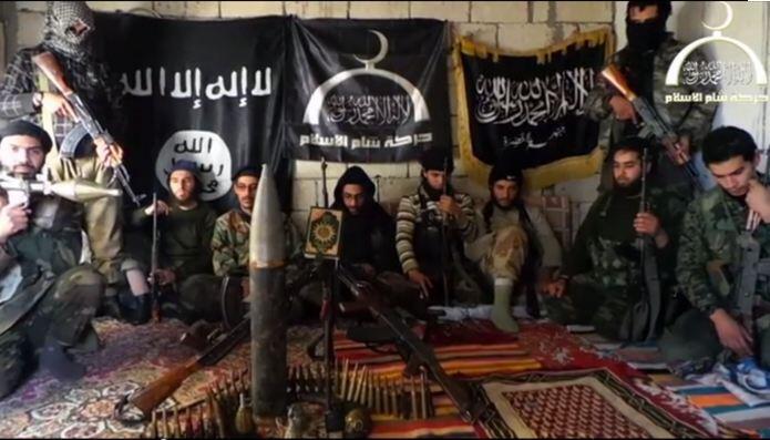 Le groupe des jihadistes marocains de Harakat Sham al-Islam. Derrière au centre, le drapeau de HSI. A droite celui du Front al-Nosra , à gauche celui de l'EIIL. Cette photographie tirée du rapport de Romain Caillet, provient d'une vidéo diffusée par HSI.