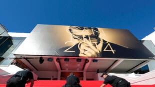 Des ouvriers deroulent le tapis rouge sur les marches du Palais des festivals de Cannes.