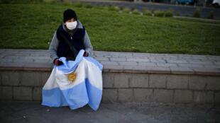 Uma mulher, segurando uma bandeira nacional argentina, senta-se em um muro de pedra durante um protesto contra uma ampla pauta de questões, incluindo a política econômica do governo e políticas estatais para combater a propagação da Covid-19, em Buenos Aires, Argentina, sábado, 19 de setembro de 2020.