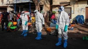 Des membres des services de santé et d'hygiène sénégalais se préparent à désinfecter les rues d'un marché de Dakar afin de lutter contre le coronavirus, le 22 mars 2020.
