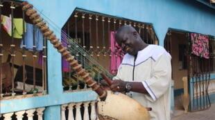 Jaliba Kuyateh joue du kora, l'instrument sacré des griots mandingues.