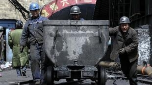 Rescue miners pull a tram car out of the Wangjialing coal mine